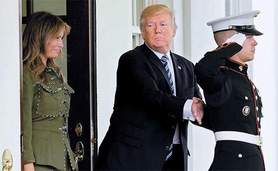 도널드 트럼프 미국 대통령(가운데)이 부인 멜라니아(왼쪽)와 함께 27일(현지시간) 미국 워싱턴 백악관에서 회담 후 떠나는 마우리시오 마크리 아르헨티나 대통령을 배웅한 뒤 백악관에 배치된 해병의 등을 두드리며 격려하고 있다. 취임 전부터 사업가로서 교류했던 두 정상은 30여 년 동안 알고 지낸 사이다. [로이터=뉴스1]