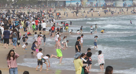 지난달 30일 부산 낮 최고 기온이 23도의 초여름 날씨를 기록하자 부산 해운대해수욕장에서 어린이와 시민이 물놀이를 하며 더위를 식히고 있다.송봉근 기자