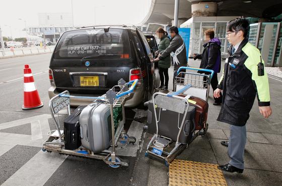 콜밴기사가 손님의 짐을 차량에 싣고 있다. 앞으로 부당요금을 받으면 즉시 해당 차량의 영업권이 정지돼 운행을 할 수 없게 된다. [중앙포토]
