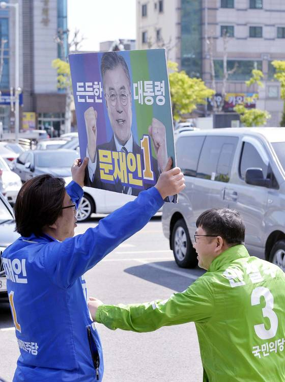 지난달 27일'어머니 생활체육대회'가 열린 대전 충무체육관 앞에서 국민의당 선거운동원이 더불어민주당 선거운동원의 배를 장난스럽게 만지고 있다. 사진공동취재단