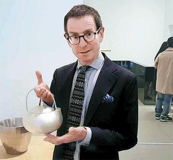 """가이 샐터 런던크래프트위크 회장이 2일 전통 방짜 기술을 적용한 정유리 작가의 은주전자를 들어보이고 있다. 그는 """"아름지기처럼 생활용품 속 작품들을 찾아 전시하고 싶다""""고 했다. [런던=김성탁 특파원]"""