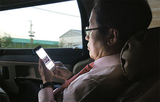 홍준표 자유한국당 후보가 3일 오후 부산 비프광장 등에서의 유세를 끝내고 대구로 향하는 승합차 안에서 자신의 휴대전화를 들여다보고 있다. [백민경 기자]