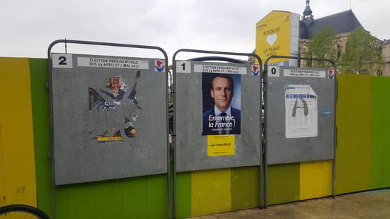 결선투표가 실시된 7일 프랑스 파리 중심가 투표소 인근 게시판에 극우 마린 르펜 후보의 선거벽보가 심하게 훼손돼 있다. 오른쪽은 에마뉘엘 마크롱 후보의 벽보. 파리=김성탁 특파원