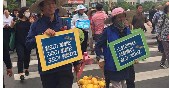 성주 주민들이 직접 재배한 참외를 들고 광화문 광장에서 미 대사관 쪽으로 향하고 있다. 홍상지 기자