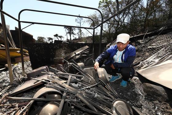 강릉시 성산면 관음리 주민 정학표씨가 7일 불타 버린 집에서 가재도구를 살펴보고 있다. [김현동 기자]