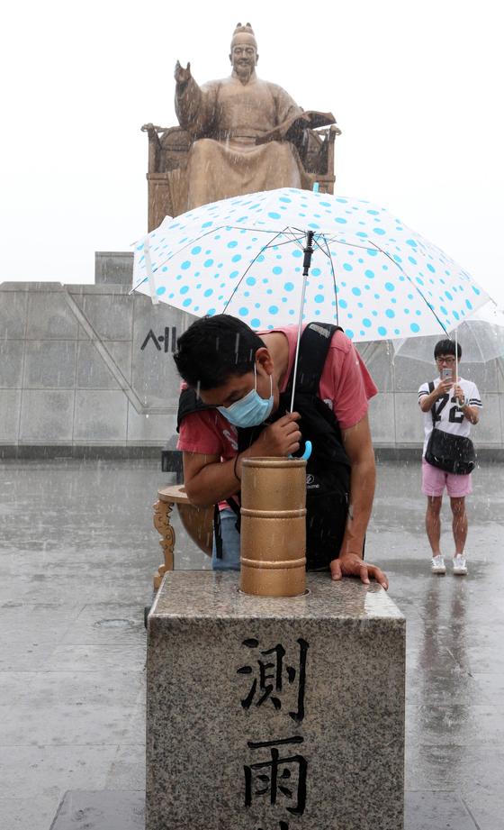 비가 쏟아지는 가운데 관광객이 서울 광화문광장에 설치된 측우기를 살펴보고 있다. [중앙포토]
