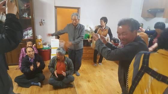 남정마을 주민들이 9일 문 후보 당선이 유력하다는 소식을 듣고 장구 장단에 맞춰 노래를 부르며춤을 추고 있다. 위성욱 기자