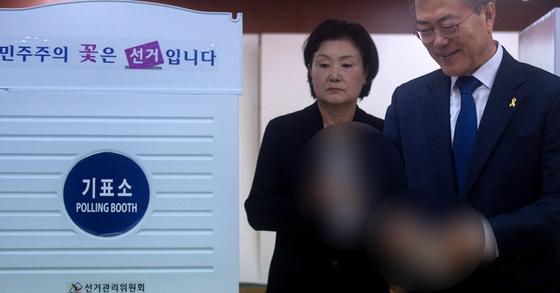 제19대 대통령 선거일인 9일 서울 서대문구 홍은중학교에 마련된 홍은 제2동 제3투표소에서 문재인 더불어민주당 후보와 부인 김정숙 여사가 투표하고 있다. [뉴시스]