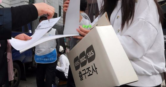 제20대 국회의원선거일인 13일 서울 중구 명동 주민센터에 마련된 명동 제1투표소 앞에서 방송3사의 출구조사원들이 유권자들을 상대로 출구조사를 하고 있다.