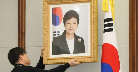 지난 2013년 2월 26일 서울 용산구 국방부 대회의실에서 한 관계자가 전날 제18대 대통령에 취임한 박근혜 전 대통령의 사진을 걸고 있다. [사진 중앙포토]