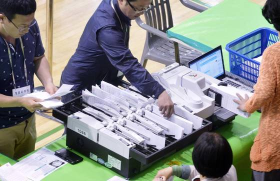 제19대 대통령선거가 마감된 9일 오후 대전 충무체육관에 마련된 대선 개표소에서 개표사무원들이 속속 도착한 투표함을 개표하고 있다. 사진 : 김성태
