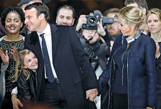 7일(현지시간) 프랑스 대통령에 당선된 에마뉘엘 마크롱(왼쪽 두번째)이 25세 연상의 부인 브리지트 트로노(오른쪽)와 당선 축하 행사에 참석해 손녀(왼쪽)를 팔로 감싸 안고 얘기하고 있다. 손녀는 브리지트가 전 남편 사이에 둔 세 자녀 중 한 명의 딸이다. 2007년 결혼한 마크롱과 브리지트 사이엔 자녀가 없다. [로이터=뉴스1]