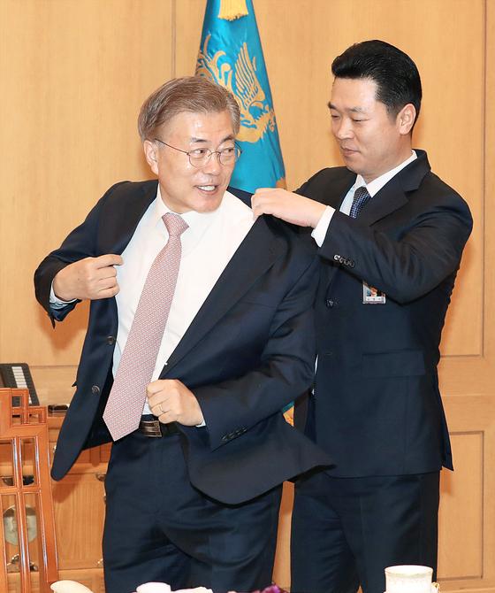 1. 청와대 직원이 문재인 대통령의 재킷을 받으려 하고 있다.
