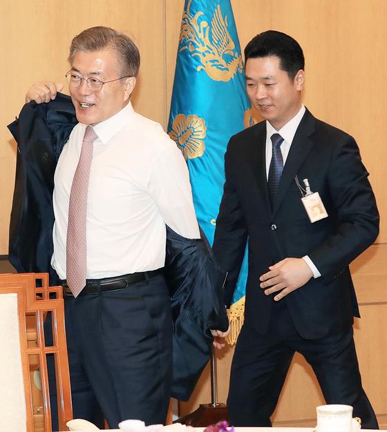 4. 문재인 대통령이직접 재킷을 벗고 있다.