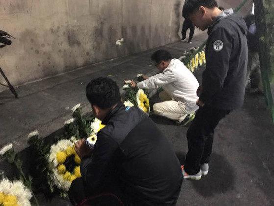 유치원 버스 화재로 한국?중국 어린이 11명이 사망한 중국 산둥성 웨이하이시 타오자쾅터널 사고 현장에서 10일 오후 부모들이 검게 그을린 바닥을 바라보며 오열하고 있다. 전날 이 터널에서 유치원 통학 버스가 쓰레기 수거 차량과 충돌해 불길에 휩싸이는 사고가 발생했다. [웨이하이=신경진 특파원]