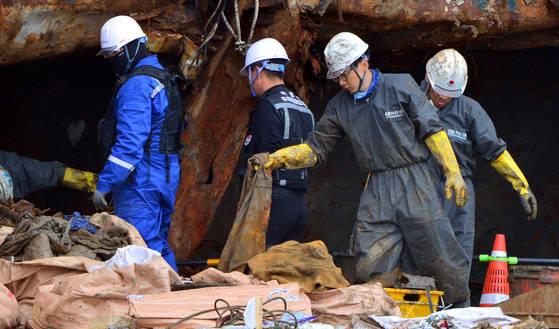 세월호에서 다수의 유골이 발견된 12일 전남 목포신항에서 감식단이 선체를 수색하고 있다. [뉴시스]