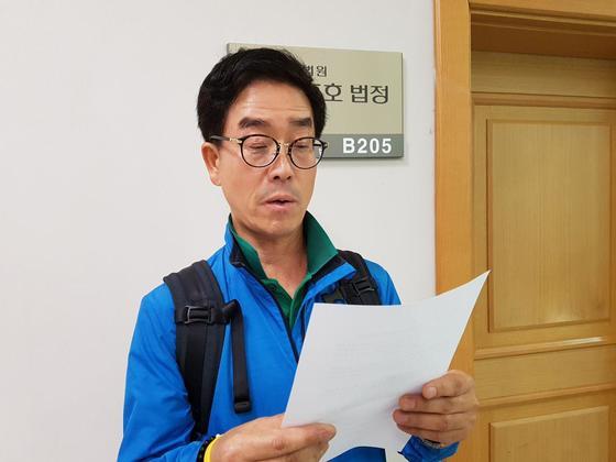 세월호 사고로 희생된 안산 단원고 김초원 교사의 아버지 김성욱씨가 딸의 순직을 인정해달라며 낸 재판이 열린 11일 서울행정법원 법정 앞에서 호소문을 미리 읽어 보고 있다. 유길용 기자