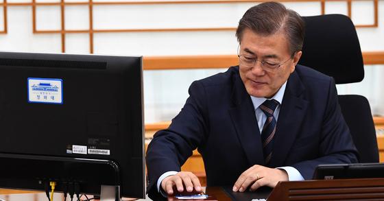 문재인 대통령이 12일 여민관 집무실에서 전자서명에 앞서 컴퓨터 접속을 위해 카드로인증을 하고 있다. [사진 청와대 사진기자단]