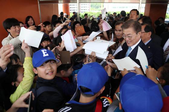 문재인 대통령이 15일 오후 서울 양천구 은정초등학교에서 열린 '미세먼지 바로 알기 교실' 행사를 마친 뒤 학교를 떠날 때 학생들이 문 대통령에게 사인공세를 펴고 있다. 청와대사진기자단