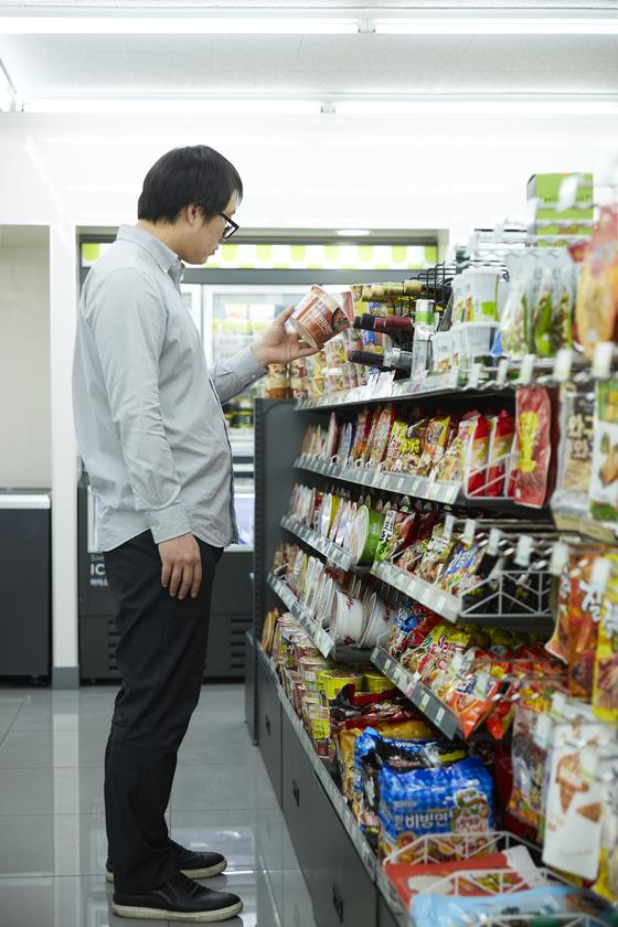 한 소비자가 마트의 라면 코너에서 제품을 살펴보고 있다. 19일부터 '나트륨 함량 비교 표시제'가 시행되면 포장지만 보고도 제품이 다른 제품에 비해 얼마나 짠지를 예상할 수 있게 된다. [중앙포토]