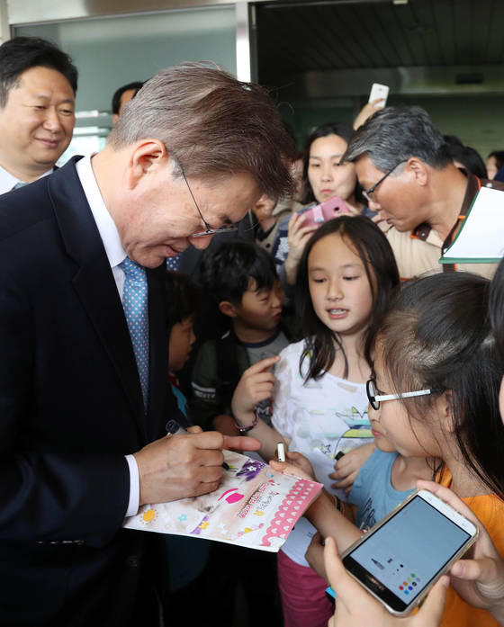 문재인 대통령이 15일 오후 서울 양천구 은정초등학교에서 열린 '미세먼지 바로 알기 교실' 행사를 마친 뒤 학교를 떠날 때 학생들에게 사인해 주고 있다. 청와대사진기자단