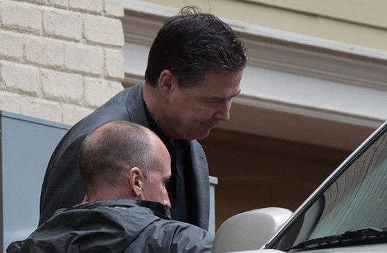 트럼프가 해임한 제임스 코미 전 FBI 국장(오른쪽)이 13일 자택에서 나오고 있다. [AP=뉴시스]