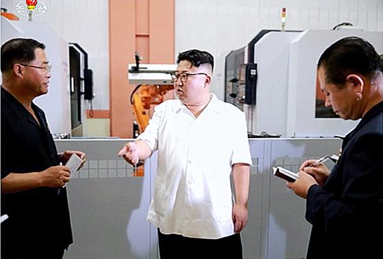 지난해 8월 10일, 조선중앙TV가 김정은 노동당 위원장 겸 국무위원회 위원장이 '1월 18일 기계종합공장'을 현지지도했다고 보도했다. 김정은 뒤에 보이는 로봇팔이 스위스 ABB사의 정밀기계로 보인다. [사진 조선중앙TV 캡처]