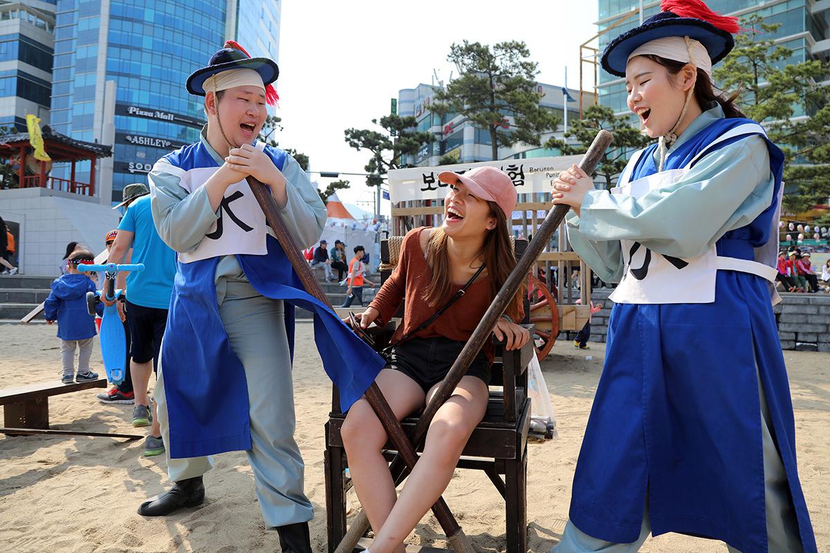 '광안리어방축제'가 열린 14일 부산 수영구 광안리해수욕장에 마련된 옛 조선 시대 형벌 체험장에서 한 시민이 주리체험을 하고 있다. 송봉근 기자