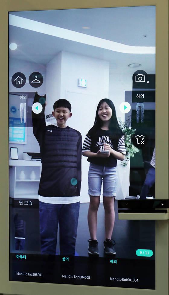 이재훈(왼쪽)·김재민 학생기자가 스마트 거울 앞에서 가상의 옷을 입어보고 있다.