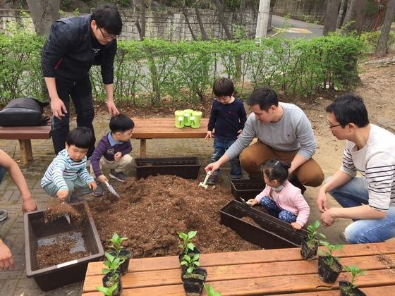 서울시 서초구가 지원하는 아빠 육아모임 '바우뫼로 파파스' 회원들이 자녀들과 꽃을 심고 있다.[사진 서초구청]