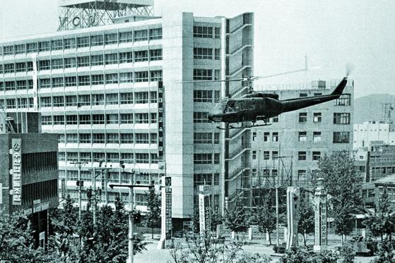 1980년 5·18 당시 전남도청 쪽에서 전일빌딩 앞쪽으로 헬기가 비행하고 있다. 왼쪽 위는 당시 150여 발의 헬기 사격에 의해 탄흔이 남아 있는 전일빌딩 10층 사무실이다. 외벽에서도 35발의 탄흔이 발견됐다. [사진 5·18기념재단]
