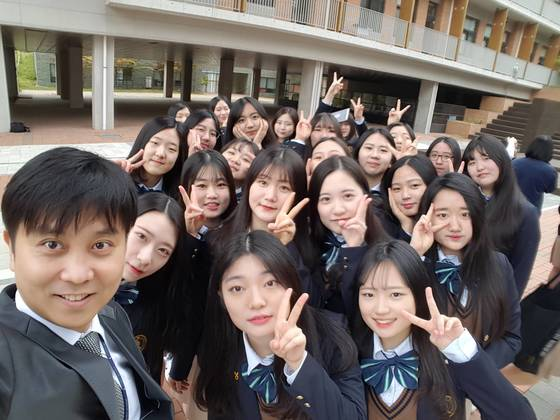 인천하늘고 김경훈 교사(왼쪽)가 담임을 맡고 있는 3학년 학생들과 교정에서 기념촬영했다. 김 교사는 밴드의 보컬을 맡고 있는 현직 가수이기도 하다. [사진 김경훈]