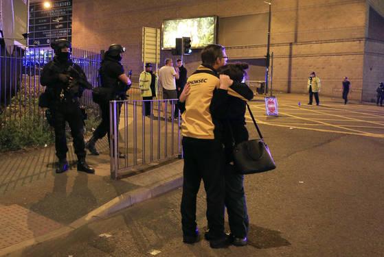 22일 밤 폭탄 테러가 발생한 영국 맨체스터 아레나 앞에서 경찰이 놀란 시민을 부둥켜 안고 있다. [AP=연합뉴스]