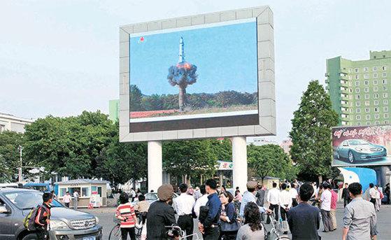 북한 평양 시민들이 지난 22일 평양역 앞에 설치된 대형 스크린을 통해 지대지 준중거리 탄도미사일 '북극성-2형'의 시험발사 장면을 지켜보고 있다. [AP=연합뉴스]