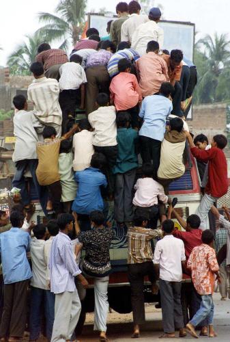 캘커타 서부 반쿠라시에서 승객들이 버스 지붕 등에 아슬아슬하게 달라붙어 있다.