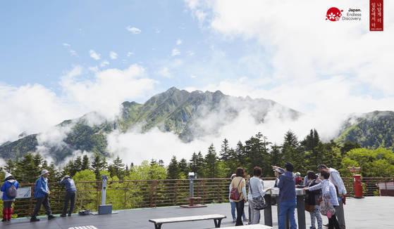 일본 100대 명산이라 불리는 도야마현 다테야마 연봉을 찾은 관광객이 경관을 감상하고 있다.