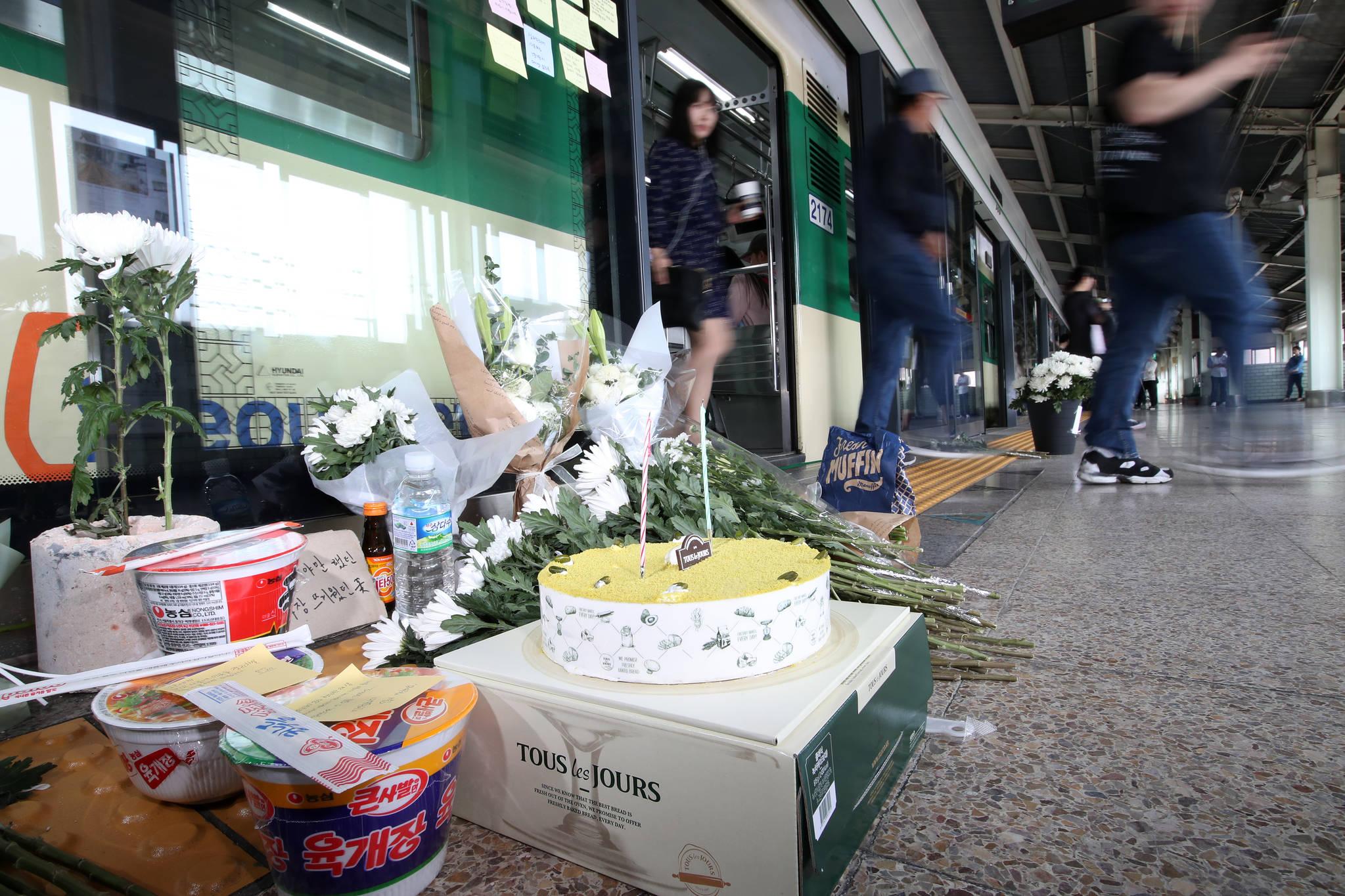 서울 광진구 지하철 2호선 구의역 스크린도어 사망 사고 1주기인 28일 당시 사고가 발생했던 9-4번 승강장 양옆으로 고인을 기리는 국화와 컵라면 케이크 등이 놓여 있다.