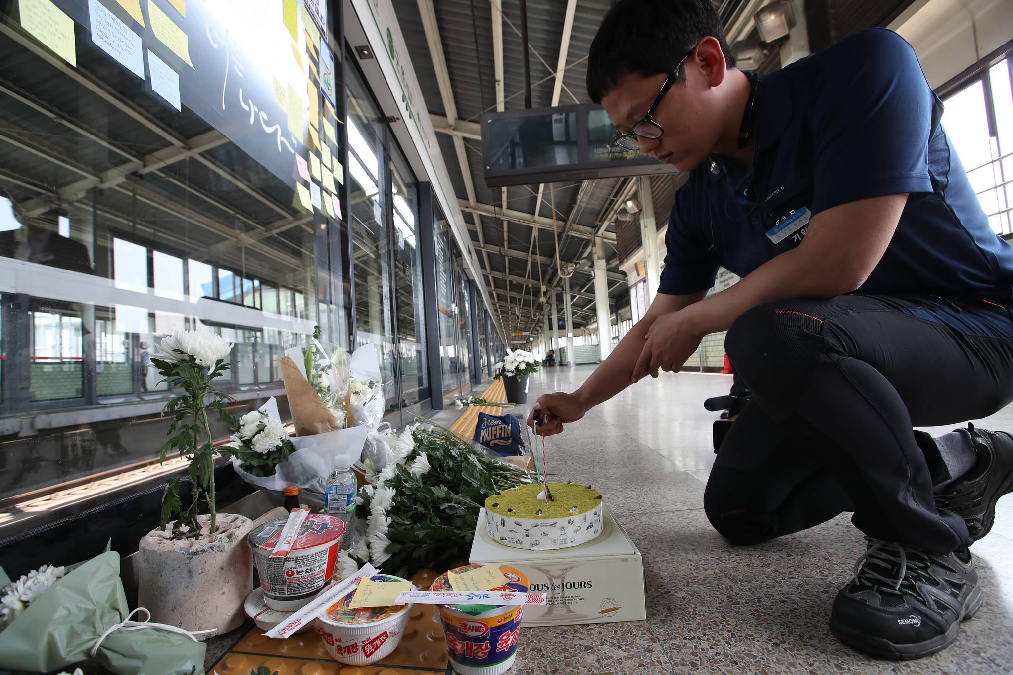 숨진 김 씨와 함께 근무했던 박창수 씨가 케이크에 불을 붙이고 있다. 김 씨는 지난해 생일을 하루 남기고 사고를 당했다.