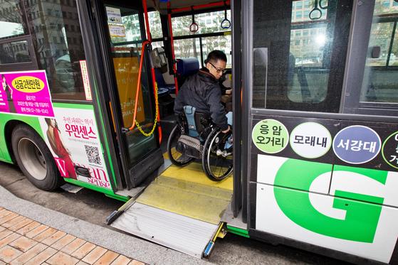 휠체어를 탄 장애인이 타인의 도움 없이 버스에 안전하게 오를 수 있도록 설계된 저상버스. 사진은 2012년 이승일 한국척수장애인협회 간사가 휠체어를 타고 저상버스 체험을 하는 모습. [중앙포토]