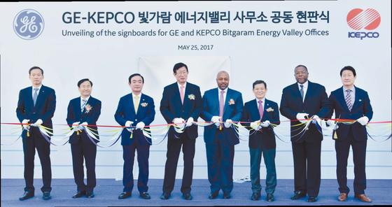 GE와 한전은 지난 25일 한전 본사와 나주혁신도시에서 'GE-한전 에너지밸리 투자 추진단 발족 행사'와 ' GE-한전 빛가람 에너지밸리 사무소 개소식'을 개최하고 빛가람 에너지밸리를 세계 최고 수준의 전력설비 통합 클러스터로 발전시킬 계획이라고 밝혔다. 'GE-KEPCO 빛가람 에너지밸리 사무소 공동 현판식'에서 한전 조환익 사장(왼쪽 넷째), GE 러셀 스톡스 에너지커넥션 사장(왼쪽 다섯째) 등 참가자들이 테이프 커팅을 하고 있다. [사진 한국전력]