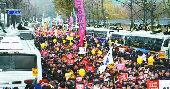 지난해 12월 3일 6차 촛불집회에 참여한 시민들이 청와대 인근 도로에서 행진하고 있다. 경복궁 담 너머로 청와대 본관이 보인다. [중앙포토]