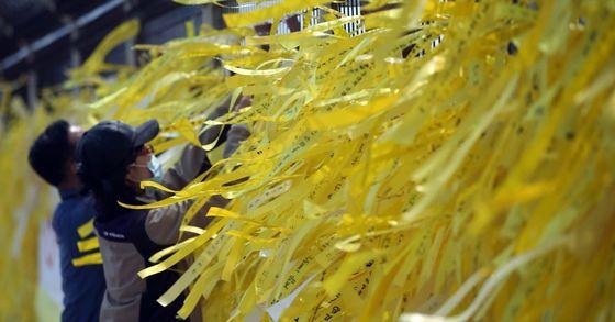 목포 신항을 찾은 시민들이 세월호가 바라보이는 철조망에 노란 리본을 매달고 있다. [중앙포토]