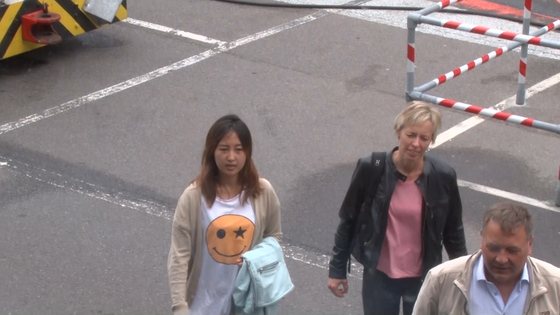 코펜하겐 공항 활주로에서 포착된 정유라.MBC 영상에 포착된 정씨는 스마일 무늬가 있는 흰 티셔츠에 베이지색 카디건을 입고 옥색 겉옷을 팔에 걸친 채 활주로를 이동했다. [MBC 캡처]