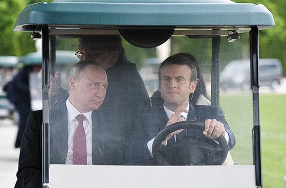 에마뉘엘 마크롱(오른쪽) 프랑스 대통령이 블라디미르 푸틴 러시아 대통령을 카트에 태우고 파리 외곽 베르사유궁 안뜰을 이동하고 있다. 마크롱 취임 후 첫 만남이다. 푸틴은 양국 수교 300주년을 맞아 프랑스를 공식 방문했다. 마크롱 대통령은 껄끄러운 러시아와의 관계를 리셋하겠다고 밝혔다. [TASS=연합뉴스]