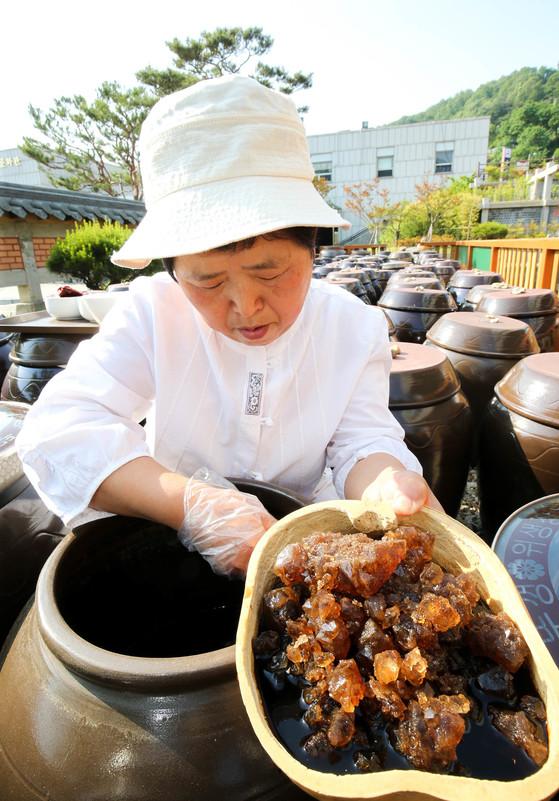 함씨네밥상 함정희(64·여) 대표가담근 지 10년 된간장 독에서 소금 결정체를바가지로 퍼올리고 있다.[프리랜서 장정필]