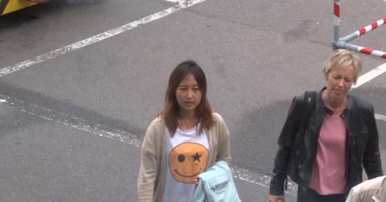 코펜하겐 공항 활주로에서 포착된 정유라씨. MBC 영상에 포착된 정씨는 스마일 그림이 있는 흰 티셔츠에 베이지색 카디건을 입고 옥색 겉옷을 팔에 걸친 채 활주로를 이동했다. [MBC 캡처]