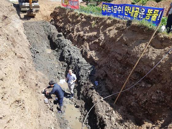 홍천군 화촌면 송정리 주민이 돈사 주변 토양과 수질 오염을 확인하기 위해 시료를 채취하는 모습. 박진호 기자