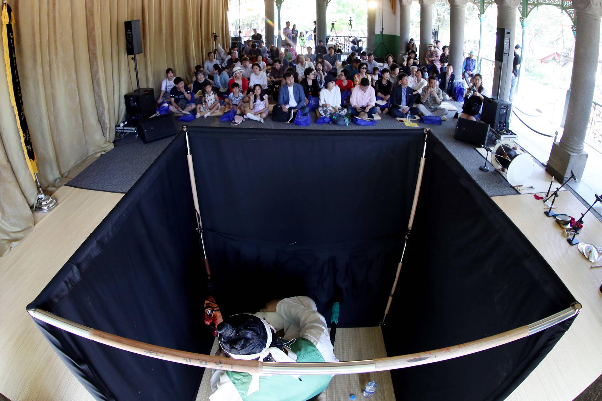 탈꾼은 검은색 천으로 가려진 좁은 공간에서 탈과 횟대를 움직인다.