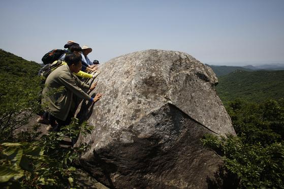 전남 해남군 두륜산에서 발견된 흔들바위를 해남군 도립공원관리사무소 직원들이 밀어보고 있다. 1816년 발간된 『대둔사지(大芚寺誌)』에 기록된 이 바위는 200여 년 만에 군청 직원들에 의해 발견됐다. [사진 해남군]