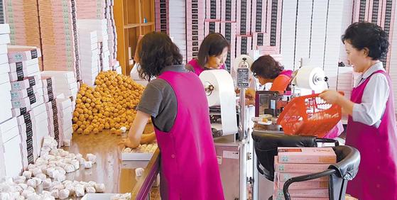천안시 구성동 매장에서 직원들이 호두과자를 포장하고 있다. [사진 학화호도과자]